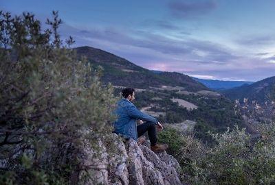 homme assis en montagne